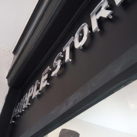 Enseigne extérieur magasins vêtements lettres plexiglas translucide effet verre avec adhésif au dos fixé avec entretoises